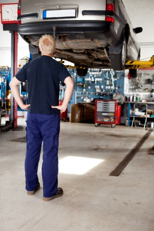 garage automobile: Un jeune m�canicien cherchant sur une voiture qui doit r�parer Banque d'images
