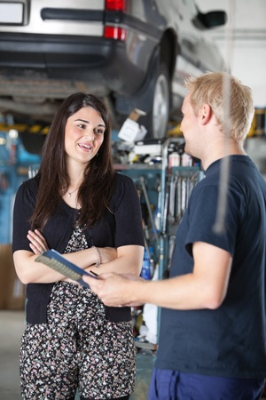 car shop: Smiling young woman and mechanic talking to each other in auto repair shop Stock Photo