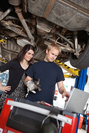 Concentrated man and woman looking at laptop while standing in garage photo