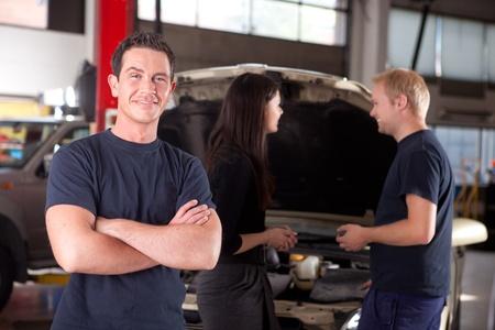 garage automobile: Portrait d'un mécanicien en regardant la caméra avec un client et deuxième mécanicien dans le fond