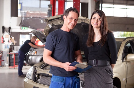 Portrait of a man mechanic with a woman customer going over the auto repair service report photo