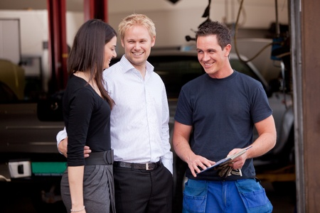 honest: A happy customer couple receiving repair summary from mechanic