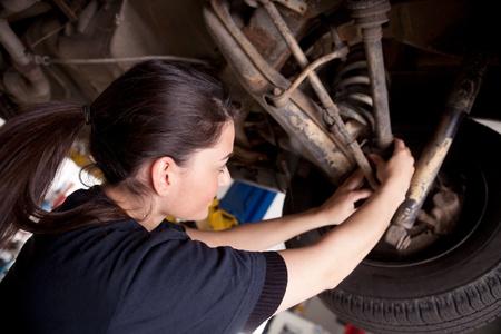 cv: Un mec�nico de la mujer trabajando en un coche, comprobando una bota de cv
