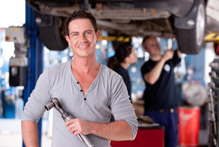 automobile workshop: Portrait of a mechanic holding an air powered socket