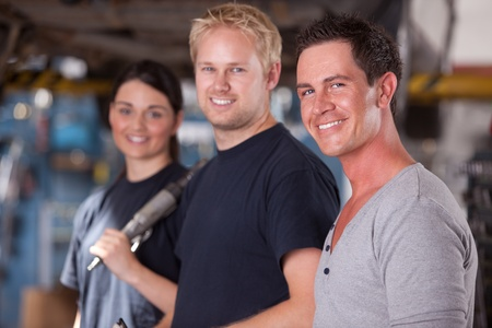 A group of three mechanics in a auto repair shop, looking at the camera photo