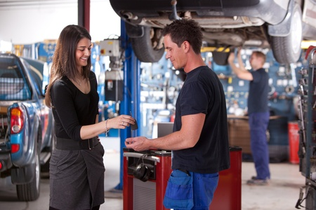 automobile workshop: A happy customer delivering a car to a auto repair shop Stock Photo