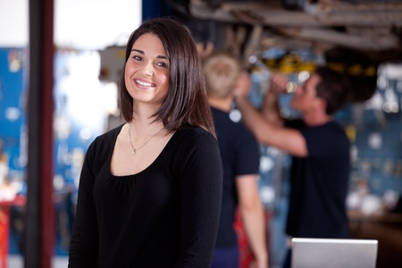 A happy woman customer in a mechanic shop, looking at the camera photo