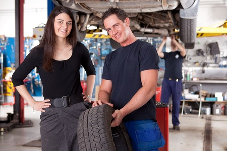 A mechanic showing a tire to a happy female customer photo