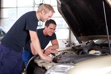 garage automobile: Deux m�caniciens homme souriant et en travaillant sous le capot d'une voiture, la profondeur de champ, mise au point nette sur le m�canicien � l'arri�re