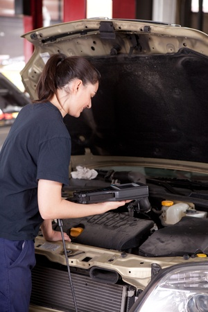 A happy woman mechanic with a smile using an engine diagnostics tool photo