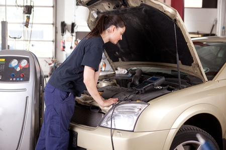 A woman mechanic tuning a car with diagnostic equipment photo