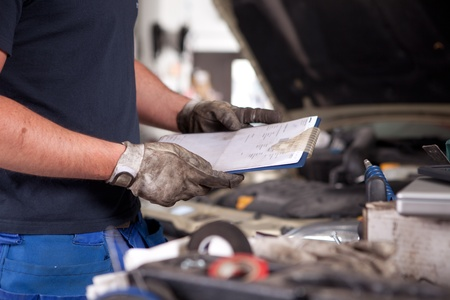 auto repair shop: Detail of a mechanic holding a service order with a dirty glove on