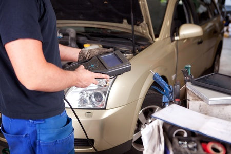 Detail of a mechanic with an electronic engine diagnostics tool photo