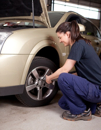 A woman mechanic loosening nuts on a wheel for a tire change photo
