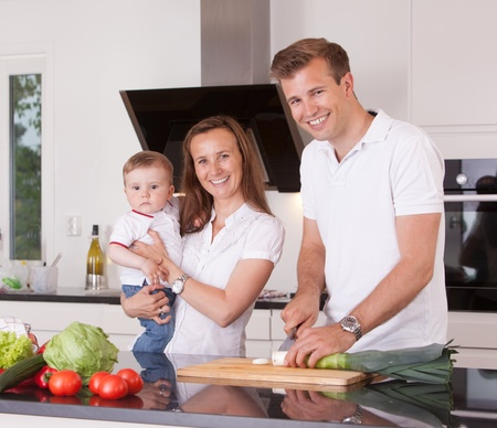 A happy family cutting vegetables in a kitchen, looking at the camera photo