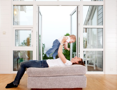 living room window: Mother holding son over head playing and having fun at home Stock Photo