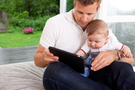 dad and baby: A father and son using a digital tablet in a home interior