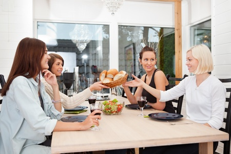 passing: Friend passing basket filled with buns at dining table Stock Photo