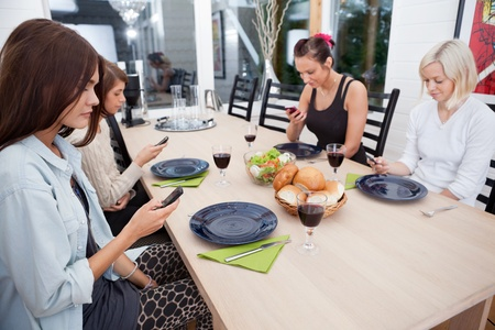 anti social: Female friends sitting at dinning table looking at cell phones
