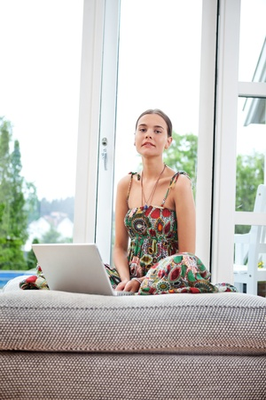Portrait of young woman with laptop on couch photo