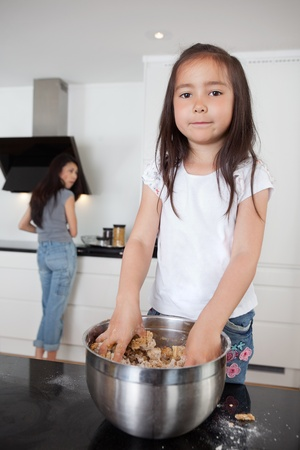 Cute girl mixing dough in kitchen with mother in background photo