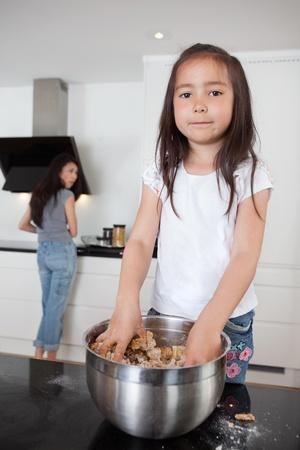 ni�os ayudando: Linda chica mezcla de masa en la cocina con madre en segundo plano