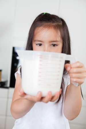 measuring cup: Little cute girl holding milk in a measuring mug