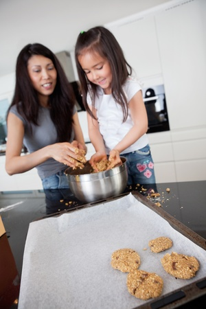 messy kitchen: Young mother with daughter in kitchen preparing cookies