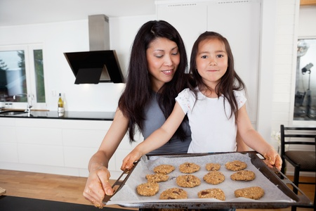 Mother and proud daughter holding sheet of cookies Stock Photo - 10536633