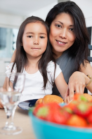 supper: Portrait of mother and her cute daughter sitting at table Stock Photo