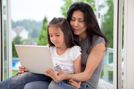 Young mother and daughter at home looking at laptop