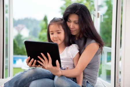 Mother and girl holding E-book reader at home photo