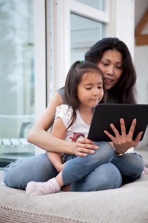using the computer: Feliz madre e hija con una tableta digital en un interior de la casa, poca profundidad de campo con enfoque cr�tico sobre el trabajo infantil Foto de archivo