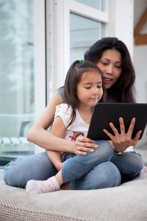 Happy mother and daughter using a digital tablet in a home interior, shallow depth of field with critical focus on child photo