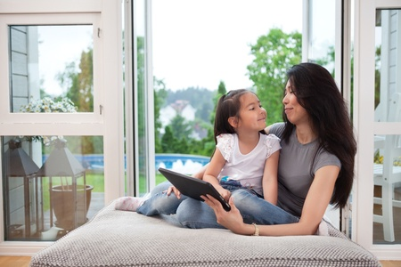 eachother: Mother and daughter at home with digital tablet, smiling at eachother Stock Photo