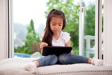 Cute young child using a digital tablet in a home interior with large window photo
