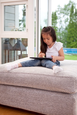 A young child playing with a digital tablet in a living room interior photo