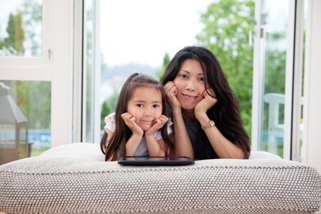 Portrait of mother and daughter lying on couch with digital tablet photo