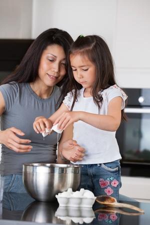 Woman teaching child to prepare dough with healthy ingredients photo