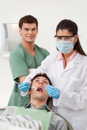 Female dentist examining mans teeth in dental office with assistant behind photo
