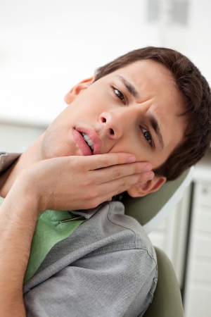 toothache: Young man holds his mouth in pain Stock Photo