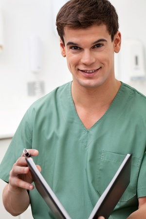 log book: Portrait of medical practitioner holding a book and smiling