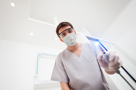 Dentist wearing mask holding UV light photo