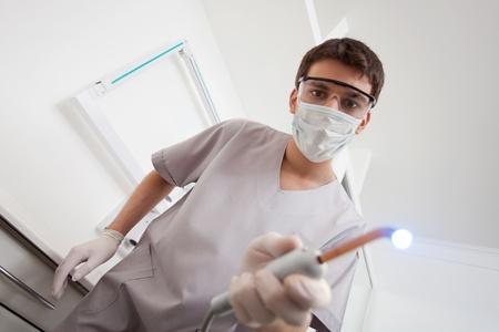 Dentist wearing mask holding medical equipment photo
