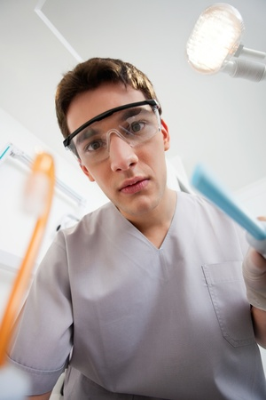 Dentist with suction hose, looking in patients mouth. Stock Photo - 10536660