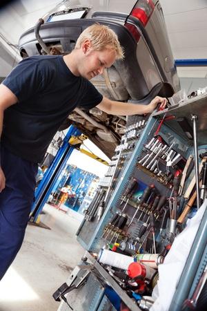 garage automobile: Mécanicien en regardant ses outils et l'équipement en atelier de réparation automobile