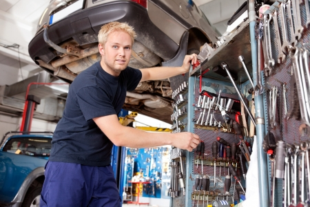 auto garage: Mechanic standing beside tool chest, looking at the camera Stock Photo