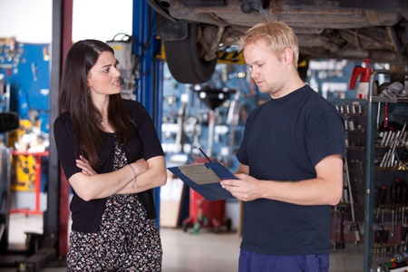 consumer: An angry customer talking to a mechanic in an auto repair shop