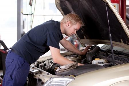 mecanico: Un joven mec�nico bajo el cap� de un coche haciendo reparaciones Foto de archivo