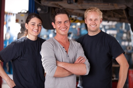 Portrait of a group of mechanics standing in a shop Stock Photo